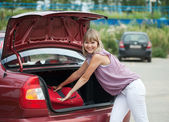 Woman packing her baggage into car — Stock Photo
