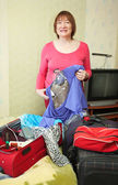 Mature woman packing suitcases — Stock Photo