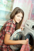 Teen girl loading the washing machine — Stock Photo