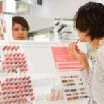 Woman is choosing lipstick — Stock Photo