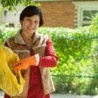 Stock Photo: Female gardener fertilizes the soil