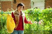Female gardener fertilizes the soil — Stock Photo