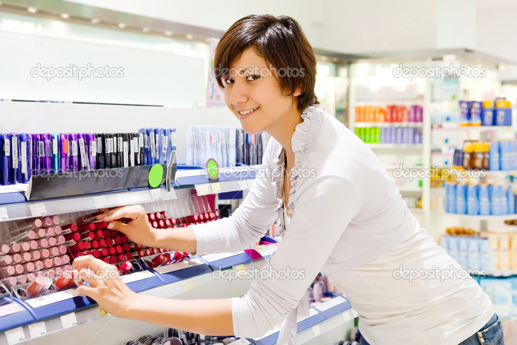 Young woman chooses the cosmetic  at cosmetics  shop  Stock Photo #9904165