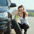 Stock Photo: Woman changing car wheel