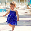 Baby girl walking at resort hotel — Stock Photo