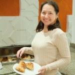 Woman takes fresh croissant — Stock Photo