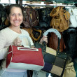 Mature woman chooses leather bag — Stock Photo #9912515