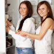 Women putting food   into refrigerator - Stock Photo