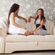 Stock Photo: Women talking on sofin home