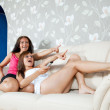 Women on sofa looking TV — Stock Photo