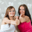 Stock Photo: Two happy women showing thumb up