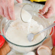 Royalty-Free Stock Photo: Cook hands adds milk into flour