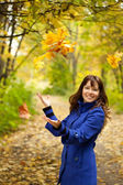 Girl throw up yellow leaves — Stock Photo
