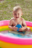 Happy baby swimming in inflatable pool — Stock Photo
