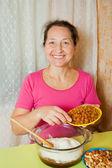 Женщина добавляет изюм в тесто — Стоковое фото