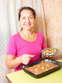 Mature woman adds nuts into dough. — Stock Photo