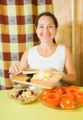 Woman adds grated eggs and sliced olives in mince — Stock Photo