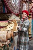 Mature woman chooses rug — Stock Photo