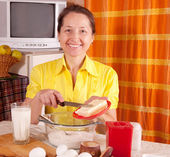 Woman adds margarine into dough — Stock Photo