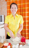Woman making dough in kitchen — Stock Photo