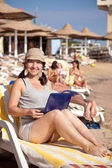 Happy woman with laptop at resort beach — Stock Photo