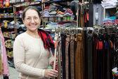 Mature woman chooses leather belt — Stock Photo