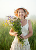 Mature woman gathers herbs — Stock Photo