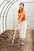 Woman working with rake in hothouse — Stock Photo