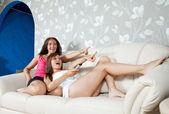 Women on sofa looking TV — Stock Photo
