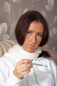 Woman sitting on sofa with thermometer — Stock Photo