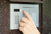 Finger pushing button of intercom — Stock Photo