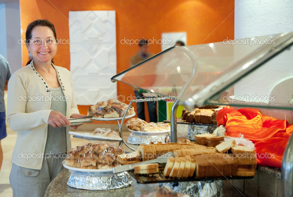 Mature woman chooses sweet pastry in buffet at hotel — Stock Photo #9912516