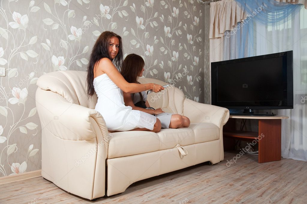 Mid adult women on sofa looking TV — Stock Photo #9912690