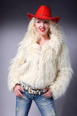 Curly blonde in a red hat and white fluffy fur coat — Stock Photo