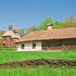 Ukrainian old log hut and church — Stock Photo