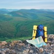 Map and tourist backpack in mountains — Stock Photo