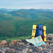 Map and tourist backpack in mountains — Stock Photo #9839653