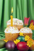 Colored eggs and Easter cakes with a lit candle — Stock Photo