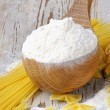 Wooden spoon with flour and pasta — Stock Photo