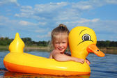 Little girl bathes in river in inflatable duck — Stock Photo