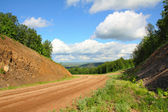 Dirt road in mountains — Stock Photo