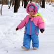 Baby girl walking in winter park - Stock Photo