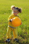 Little girl with ball on meadow — Stock Photo