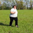 Overweight woman running on meadow — Stock Photo