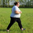 Stock Photo: Overweight womrunning on meadow