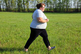 Overweight woman running on meadow — Stockfoto