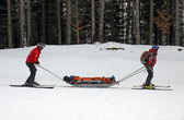 Ski rescuers are transporting injured skier — Stock Photo