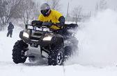 The quad bike driver rides over snow track — Stock Photo