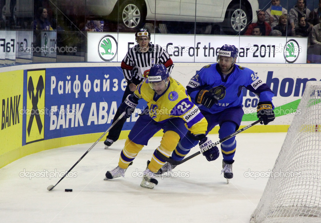 KYIV, UKRAINE - APRIL 23, 2011: Dmytro Tsyrul of Ukraine (L) fights for a puck with Dmitri Upper of Kazakhstan during their IIHF Ice-hockey World Championship DIV I game on April 23, 2011 in Kyiv — Stock Photo #9813361