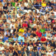 Blurred crowd of spectators on a stadium tribune — Stock Photo #9918239